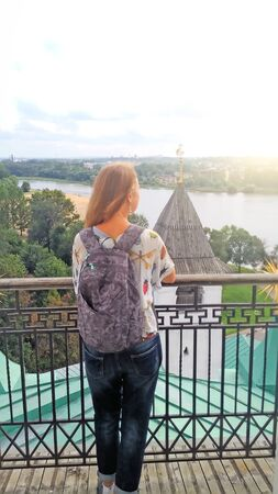 A girl with a backpack on her back is standing with her back and looking into the distance. Traveler. Russia, the City of Yaroslavl.