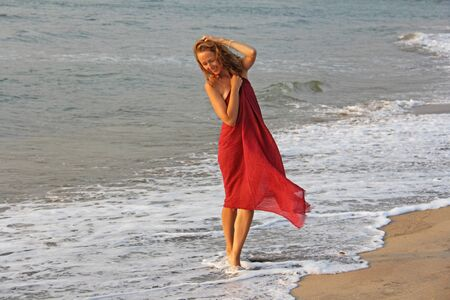 A beautiful girl with blond hair, in a red dress, walks along the seashore and smiles. Summer girl on the sea. Tenderness, alone with nature, pacification. Zdjęcie Seryjne - 133475573
