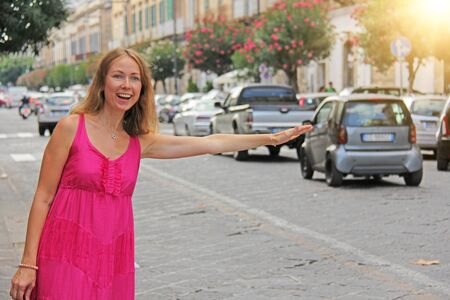 Young Romantic Girl in Summer Pink Dress Stops the Machine. Girl and the Hitchhiker. Hitchhiking on the street in Italy. Sicily Island, City of Syracuse, Italy. Zdjęcie Seryjne