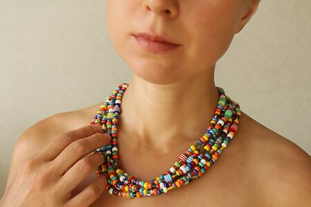 Bright beads of Murano glass on a young girl. The girl's hand touches the beads. Zdjęcie Seryjne - 133475578