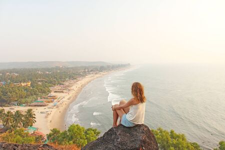 A young girl with blond hair sits on top of a mountain and looks at the sea and beach of the village of Arambol, Goa, India. The beach from a height. Relax and relax alone with nature. Zdjęcie Seryjne - 133475584