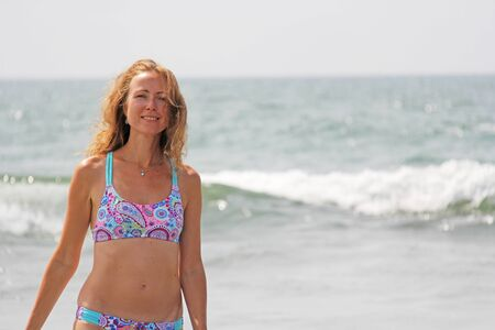 A young and beautiful girl, wearing sunglasses, in a beautiful separate swimsuit and blond hair, stands and smiles against the background of the sea. A beautiful portrait. Relax and relax.