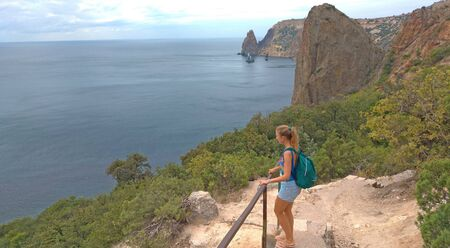 Girl with a backpack on the observation deck on the background of mountains and the sea. Beautiful scenery, vacation, vacation, solitude, relaxation. Zdjęcie Seryjne