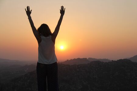 The girl at sunset. The girl stands with her back on the top of the mountain and looks at the sunset, welcomes the sun with her hands up, in Hampi. Meditation, alone with nature, silence. Hands up. Zdjęcie Seryjne