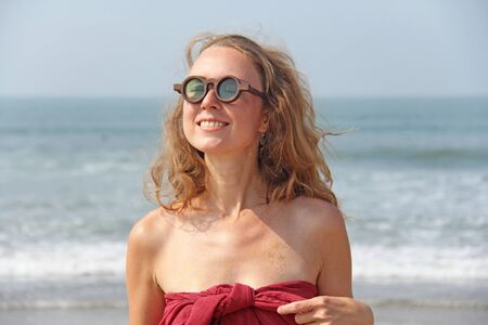 Beautiful girl freak in a red dress and blond hair, on the background of the sea. Summer girl in round wooden glasses, smiling. Unusual glasses. Zdjęcie Seryjne
