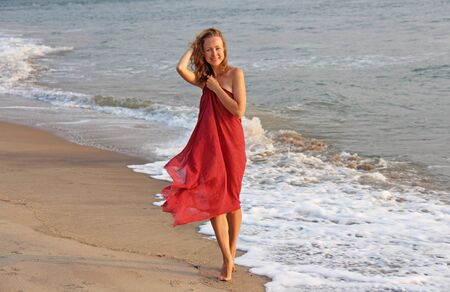 A beautiful girl with blond hair, in a red dress, walks along the seashore and smiles. Summer girl on the sea. Tenderness, alone with nature, pacification. Zdjęcie Seryjne