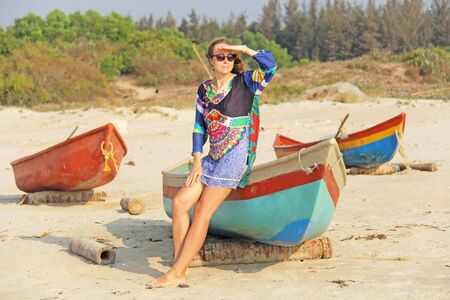Young and beautiful girl in sunglasses, with blond hair, sitting on a boat, smiling on the beach and looking at the sea. A girl in a bright summer dress. Indian boats. Zdjęcie Seryjne - 133475617