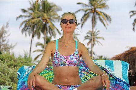 A young and beautiful girl, wearing sunglasses, in a beautiful separate swimsuit, sits in a lotus position and sunbaths on the beach under a canopy, against the backdrop of palms and blue skies. Zdjęcie Seryjne - 133475646