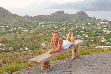 Young Lonely Girl Lies on a Bench on the Belly, with a View on the Sea and Mountains. Italy.