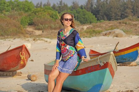 Young and beautiful girl in sunglasses, with blond hair, sitting on a boat, smiling on the beach and looking at the sea. A girl in a bright summer dress. Indian boats. Zdjęcie Seryjne - 133475649