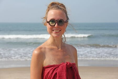 Beautiful girl freak in a red dress and blond hair, on the background of the sea. Summer girl in round wooden glasses, smiling. Unusual glasses. Zdjęcie Seryjne - 133475654