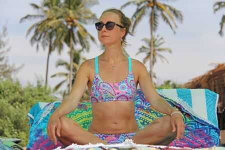 A young and beautiful girl, wearing sunglasses, in a beautiful separate swimsuit, sits in a lotus position and sunbaths on the beach under a canopy, against the backdrop of palms and blue skies. Zdjęcie Seryjne - 133475660