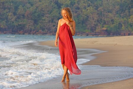 A beautiful girl with blond hair, in a red dress, walks along the seashore and smiles. Summer girl on the sea. Tenderness, alone with nature, pacification. Zdjęcie Seryjne - 133475661