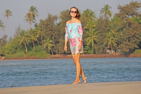 Young and beautiful girl with blond hair, in short blue and pink dress smiles and poses against the background of the sea and palms. Beautiful girl model in sunglasses. Zdjęcie Seryjne