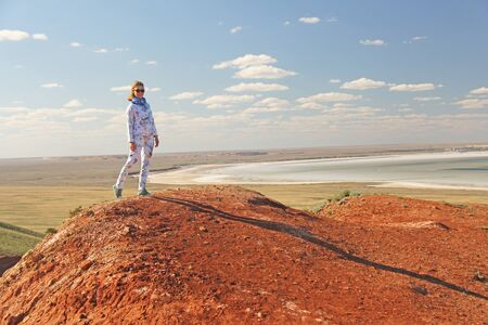 Beautiful mountains of red clay against the blue sky. Landscape of the desert. Space for text. dramatic landscape of the clay desert. The girl is standing at the top of the mountain. Zdjęcie Seryjne - 133475663