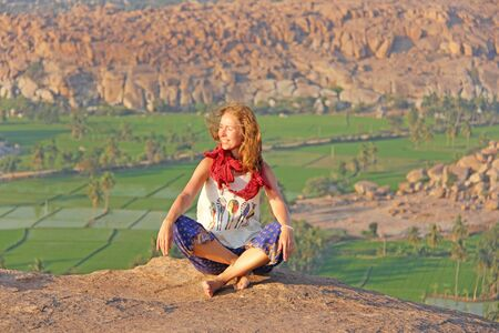 A girl in Hampi, sits and smiles on Anjaneya Hill, Hanuman Temple. Relax and rest, alone with nature. Rice fields or terraces in Hampi. Zdjęcie Seryjne
