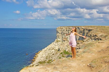 A girl in a pink dress is standing on top of a mountain, against the background of the sea. Cape Tarkhankut, Crimea. Beautiful sea summer landscape, vacation. Zdjęcie Seryjne
