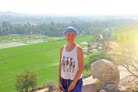 Girl tourist at the top of a mountain, in the background of green rice fields in Hampi.