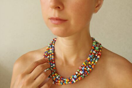 Bright beads of Murano glass on a young girl. The girls hand touches the beads.
