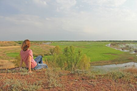 A young blonde girl in jeans and a red striped T-shirt sits with her back on the hill in summer and looks into the distance. Place for the text.