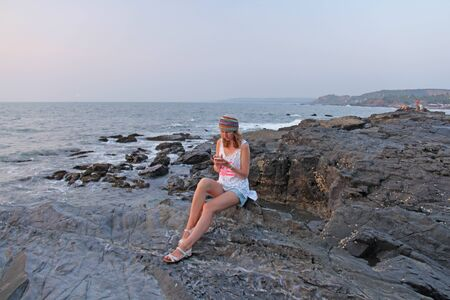 A girl in a colorful and bright hippie hat sits on a black rock and looks into the phone. India, Goa. Young girl tourist.
