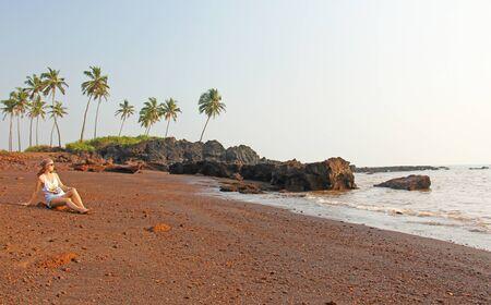 Beach with black sand and palm trees. Dark brown volcanic sand and beach in India, GOA. Zdjęcie Seryjne