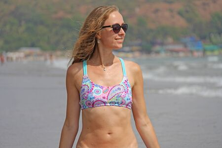 Young and beautiful girl with blond hair in a separate beautiful swimsuit smiles against the sea. India, GOA, Arambol. Beautiful summer portrait of a girl.