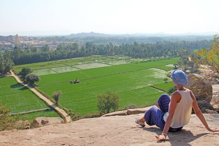 The girl is sitting with her back and looking at the rice fields of Hampi. Large stones Hampi on the side of the village of Anegundi and Virupapur Gaddi.
