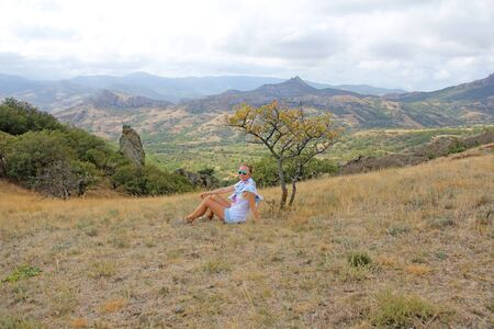 Girl on nature in the mountains. Beautiful landscape. Crimea, mountains and the sea. Summer nature.