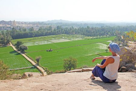 A tourist girl sits on top of Mount Hampi and looks at the green rice fields. Zdjęcie Seryjne