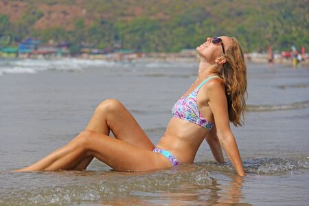 A young and beautiful girl, wearing sunglasses, in a beautiful separate swimsuit and blond hair, sits and smiles against the background of the sea. A beautiful portrait. Relax and relax.