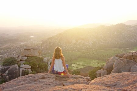 A girl sits with her back on the top of the mountain and looks at the sunset at Hampi and welcomes the sun. Meditation, harmony, alone with nature, silence. Large stones and rice fields in Hampi.