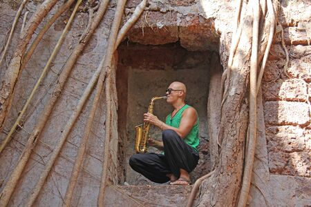 Red Fort in India, Goa. The saxophonist plays the gold alto saxophone in an unusual place, among the old fort and the roots of the trees.