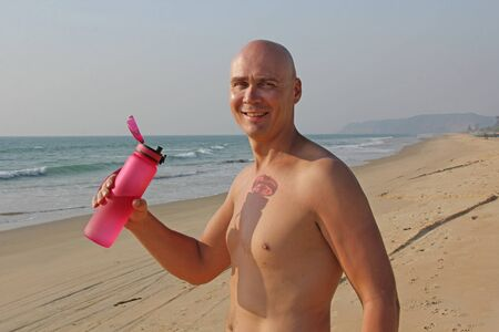 A bald, handsome man with a bare or bare torso is drinking water from a pink fitness bottle. The man is thirsty. Heat and thirst. India, Goa. Banque d'images