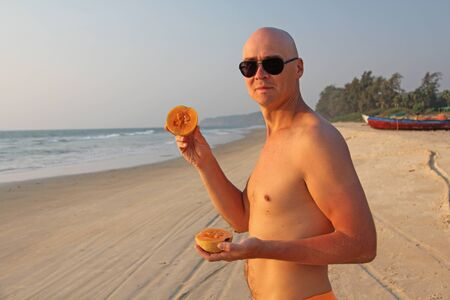 A bald and handsome man with a naked or bare torso eats a melon against the backdrop of the sea and the beach. A man is a vegetarian and a fruit. Healthy eating fruits. Proper nutrition.
