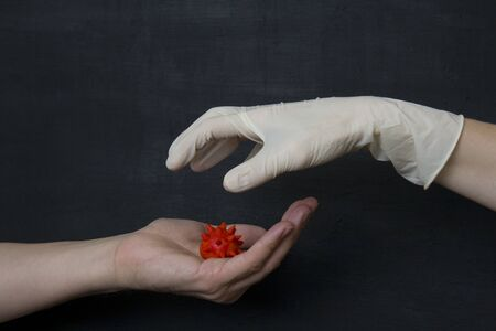 Hand without a glove holds dangerous red coronavirus, hand in white medical disposable rubber latex glove closes, destroys virus, on black background. protective disposable gloves against viruses.