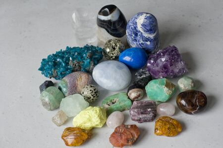 Beautiful bright multi-colored collection of natural stones and minerals from around world lies on white background. Amber, carnelian, pyrite, amethyst, emerald, agate. Beautiful stones and minerals.