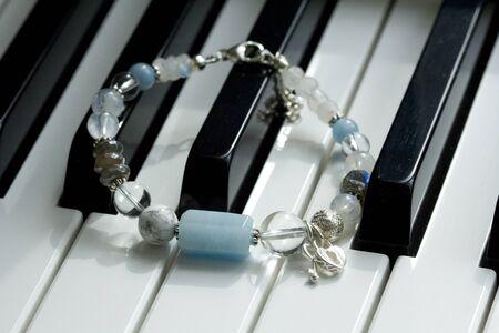 A handmade blue bracelet made of natural stones, aquamarine, cacholong, labrador, moonstone, with heart and key pendants, lies on black and white piano keys. Asymmetric arm bracelet.