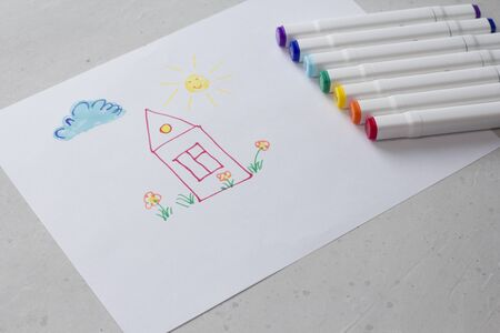 Drawn by colorful felt-tip pens a child's drawing on a white sheet of paper - a house, flowers, the sun and cloud. Creativity, drawing for children, design. Many Markers of all colors of the rainbow.