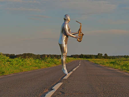 Man musician saxophonist in full body-hugging silver, silver electric suit holding golden alto saxophone, jumped and hovered in zero gravity on empty road in summer. Freak, unusual person, alien, UFO.
