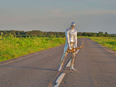 Man musician saxophonist in full body-hugging silver and silver electric suit holding golden alto saxophone, standing on empty road in summer with perspective. Freak, unusual person, alien, UFO.
