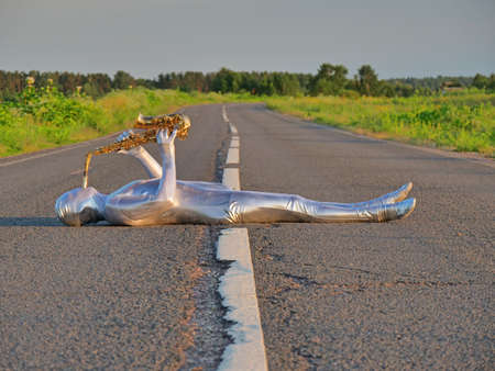 Man musician saxophonist in full body-hugging silver and silver electric suit holding golden alto saxophone, lies on empty road in summer with perspective. Freak, unusual person, alien, UFO. Archivio Fotografico