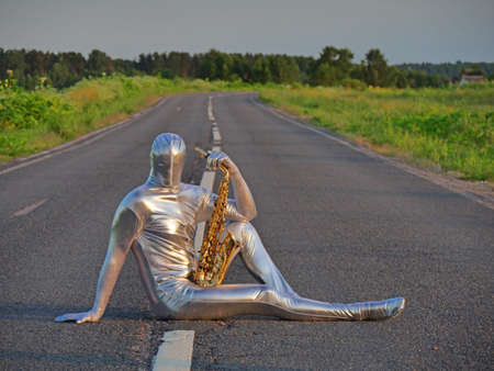 Man musician saxophonist in full body-hugging silver and silver electric suit holding golden alto saxophone, sitting on empty road in summer with perspective. Freak, unusual person, alien, UFO. Archivio Fotografico