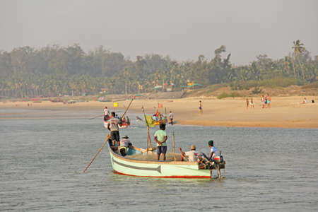India, GOA, January 19, 2018. Fishermen on boats go to sea. Fishermen in boats are fishing and swimming along the river against the backdrop of palm trees.
