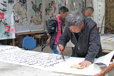 China, Suzhou - April 14, 2012. The man writes Chinese characters with a brush, calligraphy in China. The man is Chinese.