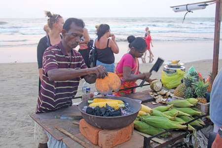 India, GOA, January 28, 2018. The seller of cooked and baked corn. Street trading in India, selling corn. Street delicious food on the beach.