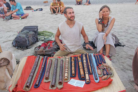 India, GOA, January 28, 2018. A man and a girl musicians, sell flutes in a street bazaar, on the beach, in the village of Arambol.