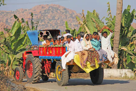 India, Hampi, January 31, 2018. Indian men ride in the back of an open truck, smile and wave their hands, say hello. Sajtókép