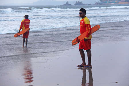 India, GOA, January 28, 2018. Men rescuers walk along the shore in red clothes, whistle in the whistle, warn of danger in the sea and expel people from the sea.