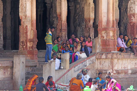 India, Hampi, 01 February 2018. A group of Indian people, bright men and women, waving hands inside the Virupaksha temple, smiling and giving greetings. Publikacyjne